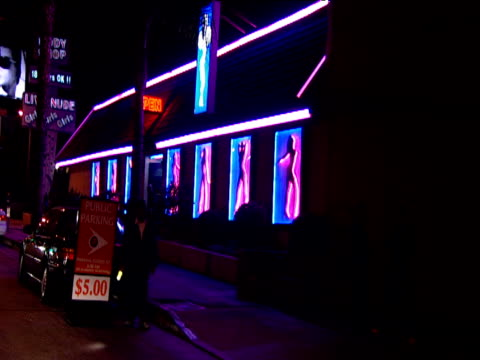 vidéos et rushes de track from car past strip club parking attendant waves neon torch to highlight entrance to car park sunset strip los angeles - peep show