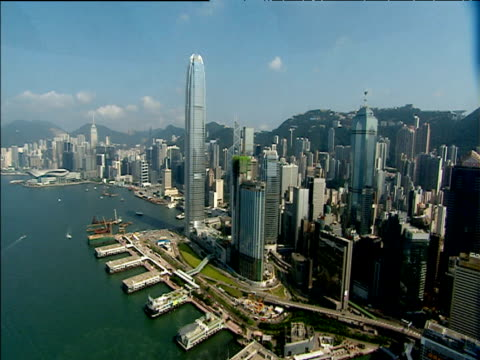 track from helicopter over harbour and skyscrapers with mountains in background hong kong - central district hong kong stock videos and b-roll footage