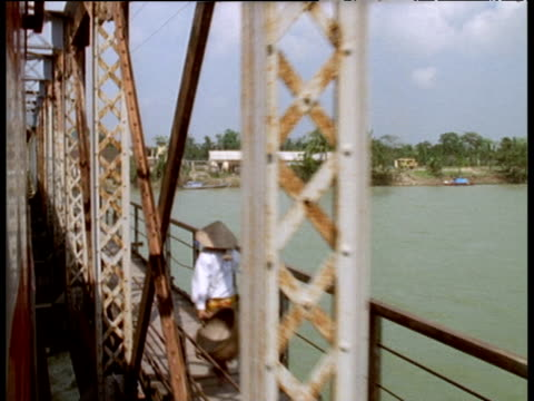 track from train railway bridge over river as people pass on walkway wearing traditional coolie hats; vietnam - railway bridge stock videos & royalty-free footage