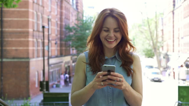 vídeos de stock e filmes b-roll de track in - young woman laughing with smart phone - 30 34 anos