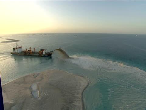 Track left above sea as sand dredger sprays sediment creating man made island Dubai