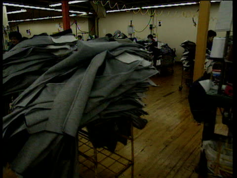 track left across machinists sewing jeans in factory - material stock videos and b-roll footage