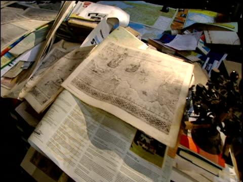 track left across old typewriter and maps laid out on large table - bbc news bildbanksvideor och videomaterial från bakom kulisserna