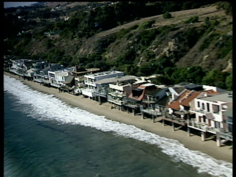Track left along beach front houses in Malibu small waves breaking along shoreline