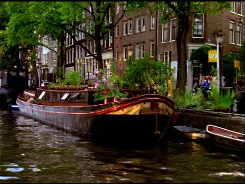 vídeos de stock e filmes b-roll de track left along canal past moored barge, amsterdam - barco casa