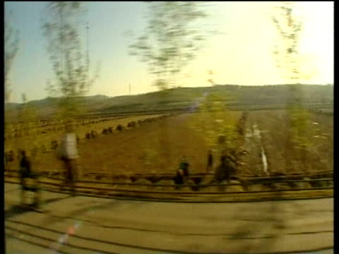 track left along rural road with labourers alongside recently harvested fields north korea; 2005 - korea stock-videos und b-roll-filmmaterial