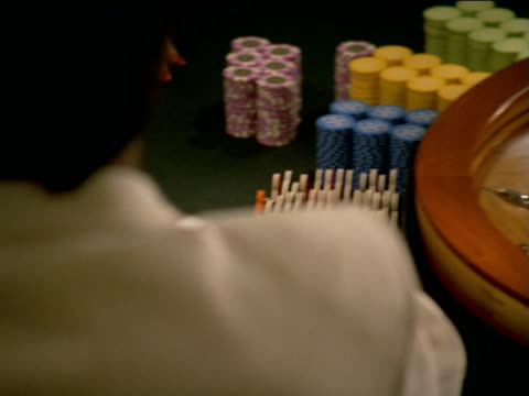 track left as roulette wheel spins, while gamblers place chips on table - loss stock videos and b-roll footage