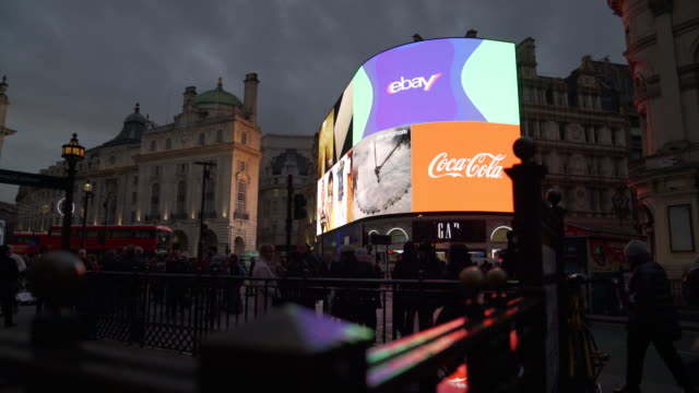 Track left as traffic and pedestrians pass in front of the bright lights of Piccadilly Circus, London