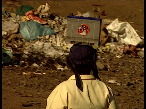 track left as woman balancing car battery on her head walks past pile of rubbish - heap stock videos & royalty-free footage