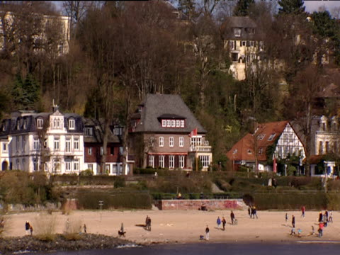 vídeos de stock, filmes e b-roll de track left from boat across busy beach with luxury houses in background set in leafy area hamburg - rio elbe