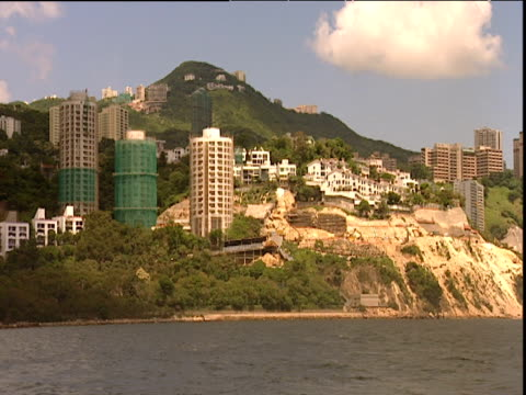 track left from boat along shore with skyscrapers and mountains hong kong - erezione video stock e b–roll
