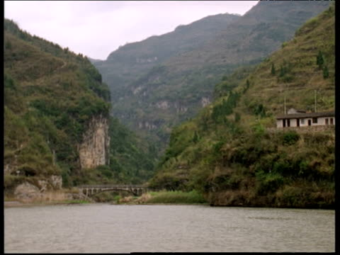 Track left from boat along Yangtze river banks past green hills and small bridge China