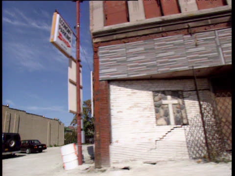 vidéos et rushes de track left from car along inner city chicago ghetto past dilapidated buildings including liquor store chicago - chicago illinois