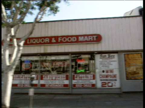 vídeos y material grabado en eventos de stock de track left from car along los angeles street past shops including liquor stores and food marts. cars parked on side of road. track past viper rooms nightclub - 1996