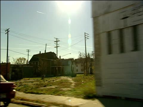 vidéos et rushes de track left from car along streets of detroit past houses derelict buildings and billboards - detroit