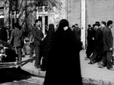 track left from car past cars and pedestrians tehran 1963 - teheran stock-videos und b-roll-filmmaterial