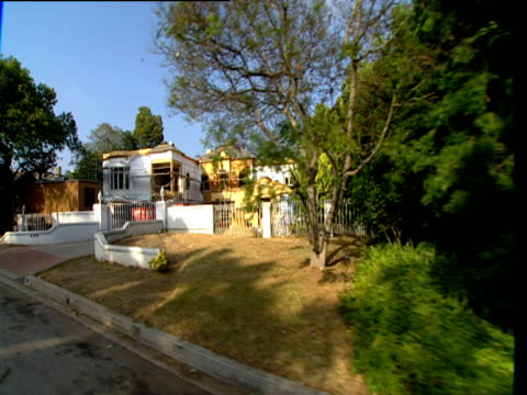 track left from car past large house under construction hollywood - erezione video stock e b–roll