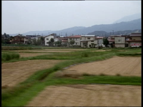 Track left from train past fields and houses Honshu Japan
