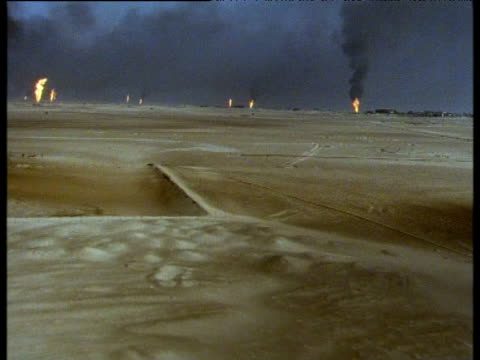 Track left over burning oil fields and smoke, Kuwait, 1991