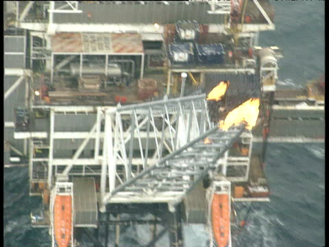 track left over flames coming out of oil rig pipe track backwards over large oil rig and boat in north sea - offshore platform stock videos & royalty-free footage