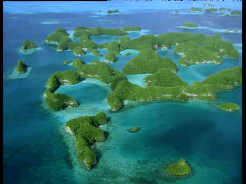 track left over green shrub covered atolls surrounded by tropical blue seas palau - palau video stock e b–roll