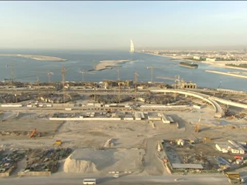 track left over huge sandy construction zone towards cranes dubai - bridge built structure stock videos & royalty-free footage