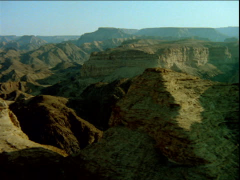 track left over rocky peaks of mountain range above river - ムラがある点の映像素材/bロール