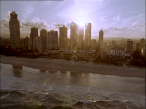 Track left over skyscrapers of Surfer's Paradise as sunlight filters through onto beach and waves in foreground