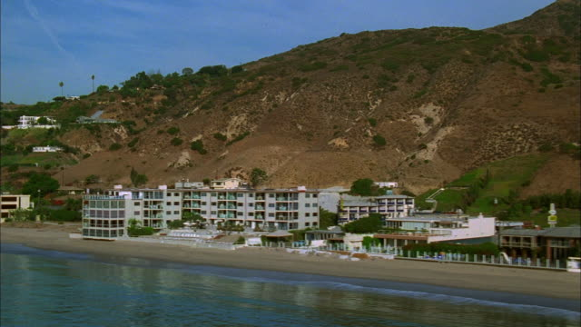 Track left past beachfront houses and shoreline, Malibu, California Available in HD.