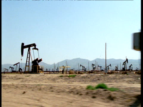 Track left past field of nodding donkey oil pumps, Bakersfield, California