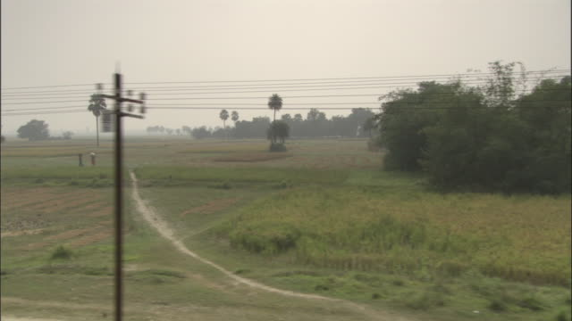 track left past fields seen from train, india available in hd. - telegraph pole stock videos & royalty-free footage