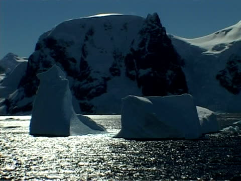 wa track left past iceberg and mountainous coastline of paradise bay area, antarctic peninsula - antarctic peninsula stock videos & royalty-free footage