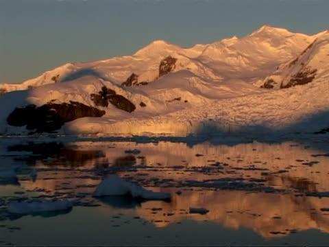 wa track left past mountainous coastline and ice floes at dusk, paradise bay area, antarctic peninsula - antarctic peninsula stock videos & royalty-free footage