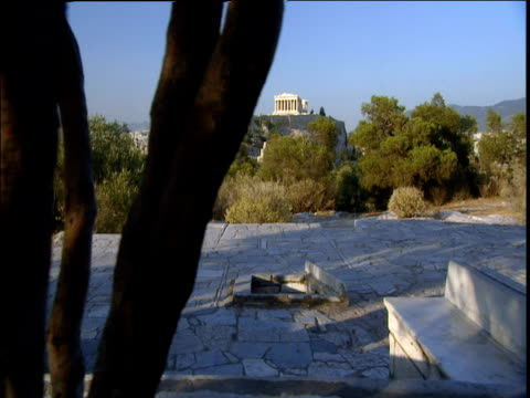 Track left though tree branches across courtyard and tree tops to Parthenon in distance blue sky Athens