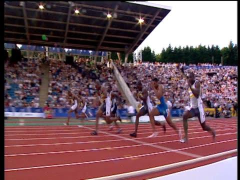 track left to follow asafa powell winning men's 100m heat 1, 2004 crystal palace athletics grand prix, london - ヒート点の映像素材/bロール