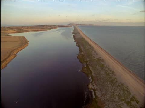 track low over chesil beach dorset - lunghezza video stock e b–roll