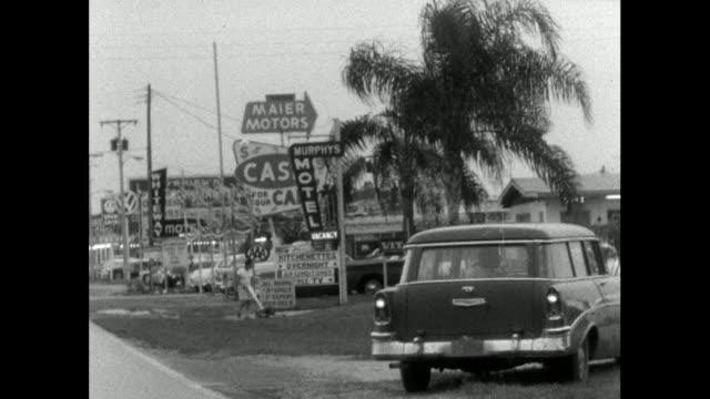 stockvideo's en b-roll-footage met track on us road past motel and retail signs; 1964 - establishing shot