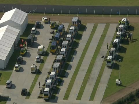 track over a large gathering of police in a field near dale farm a travellers' site in essex - デールファーム点の映像素材/bロール