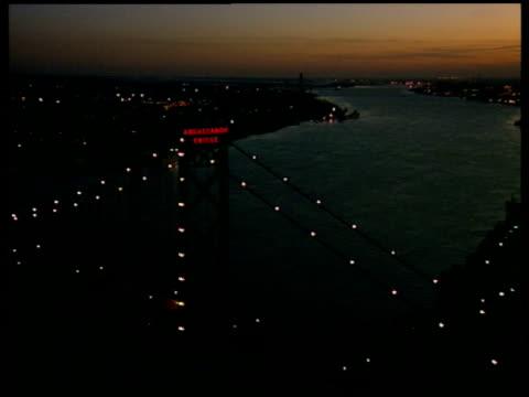 track over ambassador bridge spanning the detroit river at night - detroit river stock-videos und b-roll-filmmaterial