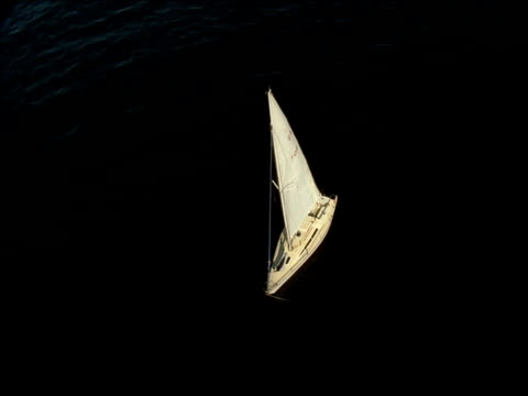 track over and around boat with sails raised floating on still water, glistening light reflected off water - menschlicher arm stock-videos und b-roll-filmmaterial