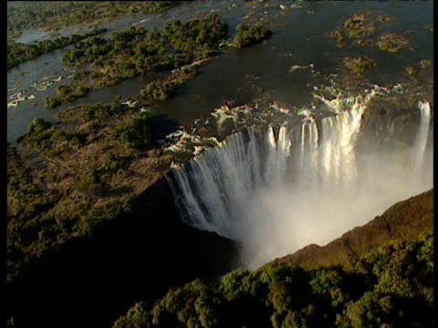 track over and around huge waterfalls running into ravine - victoria falls stock videos and b-roll footage