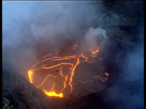 Track over and around over volcano with orange lines of lava steam and smoke rising
