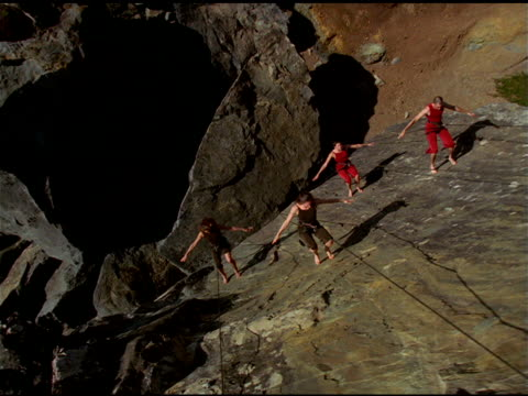 Track over Bandaloop Project dancers, attached to safety harnesses, performing acrobatic routine on cliff face, California