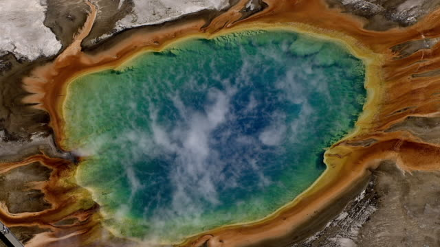 track over colourful steaming grand prismatic spring, yellowstone, usa - cianobatterio video stock e b–roll
