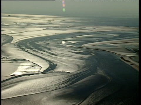 Track over expanse of glistening sand revealed by low tide Morecambe Bay
