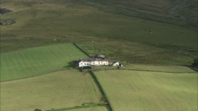 Track over farmhouse surrounded by fields. Available in HD.