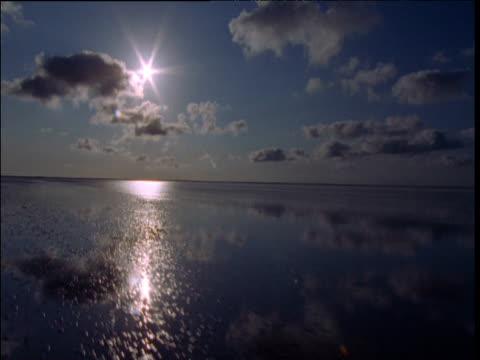 vídeos y material grabado en eventos de stock de track over flooded mud flats, sunburst in sky at dusk, broome, western australia - marea baja