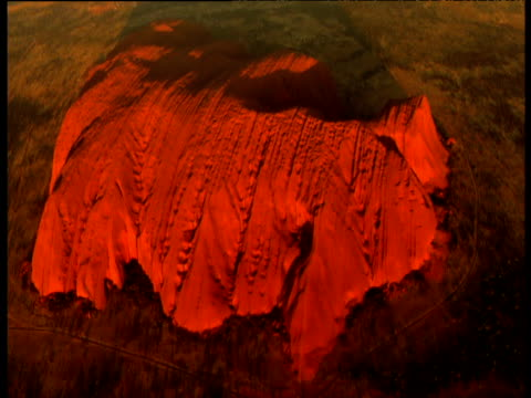 track over glowing red sandstone of uluru rising out of outback, northern territory, australia - エアーズロック点の映像素材/bロール