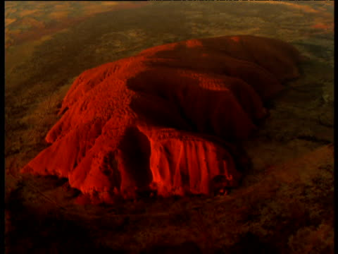 track over glowing red sandstone uluru rising out of outback, northern territory, australia - エアーズロック点の映像素材/bロール