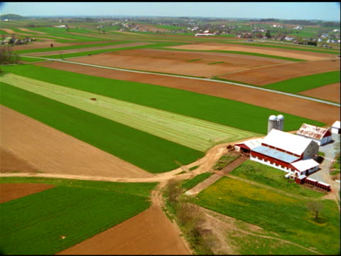 track over green pastures and zoom in to amish farmer on horse drawn harvester, pennsylvania - amish stock videos & royalty-free footage